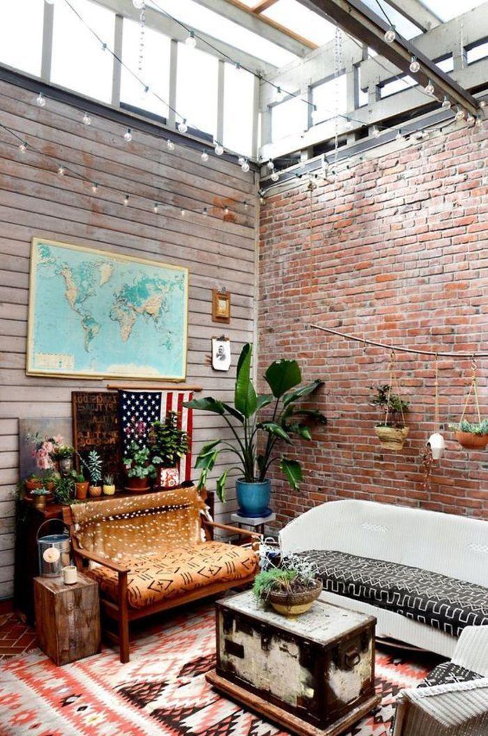 un salon chic ethnique d'esprit loft aux murs en briques et en lambris, tapis ethnique aux nuances de la terre de sienne