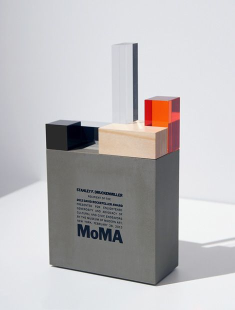 The David Rockefeller Award trophy, re-imagined by Harry Allen Design for MoMA, represents a little model of MoMA, rendered in an interpretive variety of materials, sitting on top of a cement base.