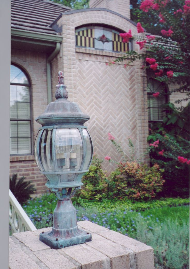 This worn exterior light fixture was repainted with an aged copper patina finish. In the background, the stained glass in the window is also a faux finish. What an excellent way to update your exterior with decorative paint finishes.