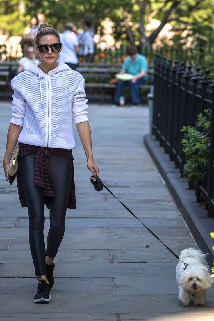Olivia Palermo  sudadera técnica de color blanco, mallas de deporte, camiseta de rayas atada a la cintura, zapatillas negras, cartera de mano bicolor y gafas de sol de pasta negra.