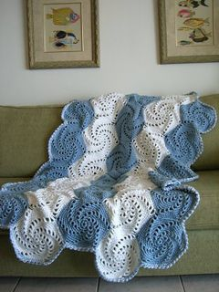 This snow-white afghan is aswirl with style! The pretty pinwheel motifs, fashioned with single crochet stitches and chain spaces, work up quickly because you use two strands of yarn. Whipstitched together, they form a simply stunning throw.