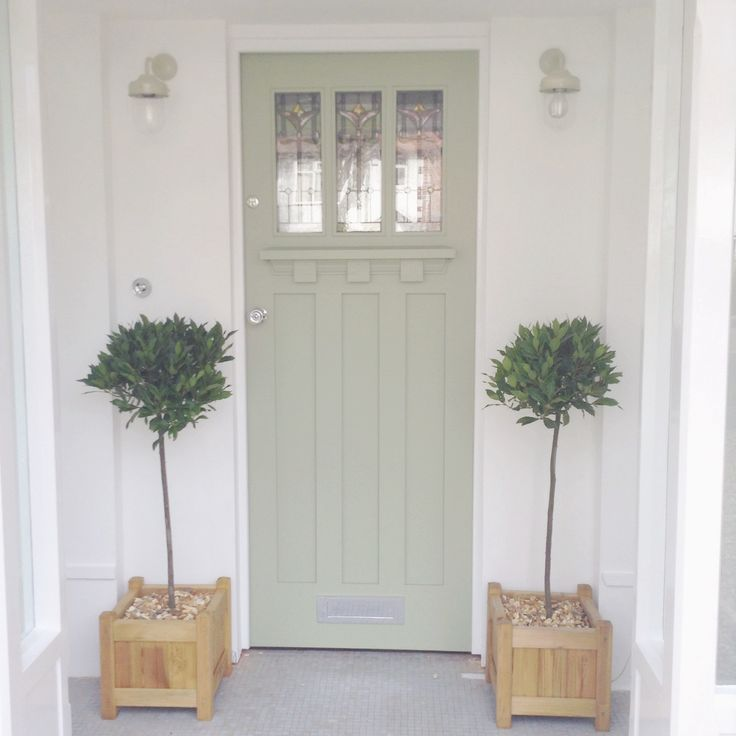 Front door painted in a Dulux colour match to Farrow and Ball Lichen. Bay trees either side below Garden Trading barn lights in clay either side. (Work in progress)