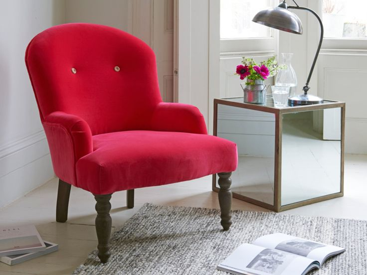 Wooden buttons, weathered oak legs and beautiful fabric. What's not to like on our classic Rosina bedroom chair? This little occasional armchair is handmade in Long Eaton, Derbyshire where the upholsterers are testament to good old-fashioned skill. Shown here upholstered in beautiful red velvet and available in over 120 gorgeous fabrics.