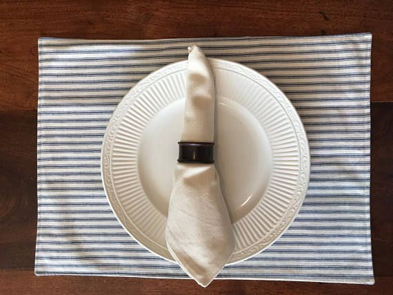 This set of 6 ticking stripe blue and cream placemats are made from a linen blend and muslin fabric. The top fabric is a linen blend blue ticking stripe fabric and the bottom fabric is a cotton muslin fabric. The two layers are machine sewn together and then then the edges are finished with a top stitch to create a clean look. These reversible placemats create the perfect place setting for a dinner party or everyday use. SIZE Generously sized at 19 inches x 14 inches. Variable by 1/2 inc...