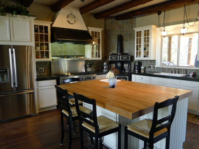 A gorgeous kitchen with Viking commercial stove and antique Monarch cook stove, in a custom mountain home I have listed near Ruidoso.