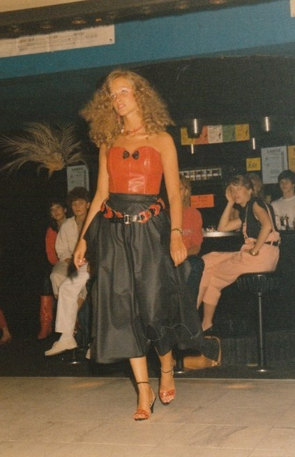 Joke with black leather skirt and red bustier.