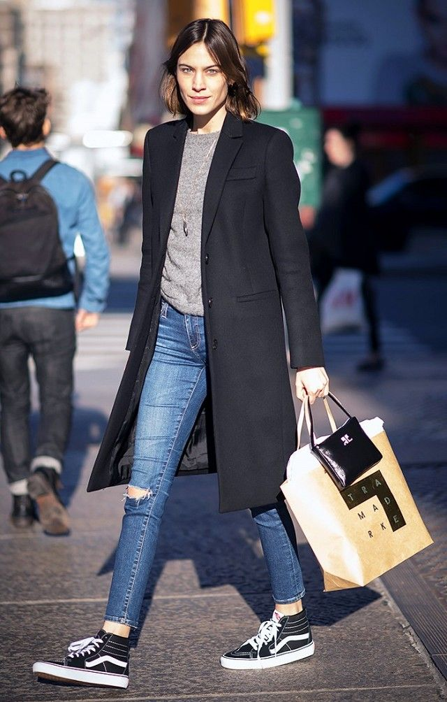 Alexa Chung is casual chic in a black coat, gray crewneck, ripped skinny jeans, and Vans Sk8-Hi Slim Sneakers