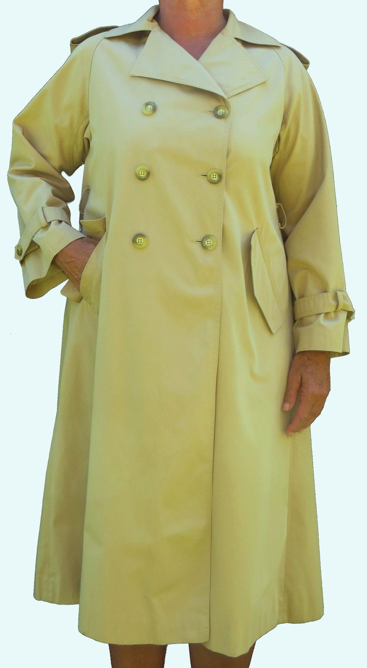 An elegant Nino Donatella all weather with a hardy outer fabric, water resistant with a full lining, double breasted, cuff ties, epaulets, a back vent, a long back pleat, missing a belt but suits a loose style with the back pleat, has two pockets, in excellent condition with fine finishes and is in a metallic light mustard or burley wood for those in the know!