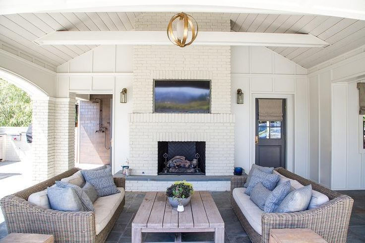 Covered patio features a vaulted ceiling accented with a brass sphere pendant illuminating a pair of wicker sofas lined with blue pillows facing each other across from a teak coffee table.