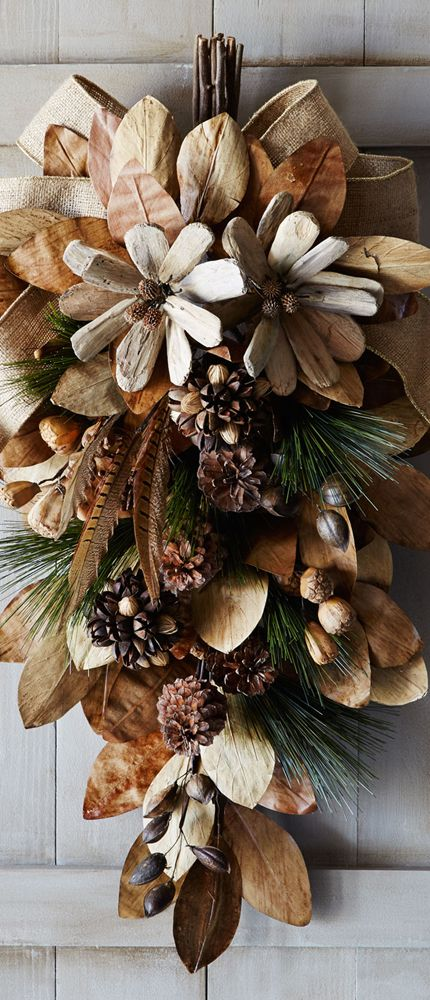 natural holiday spray with pine cones, feathers, and nuts with a burlap ribbon. (smb: I see driftwood flowers in there. How cute!)