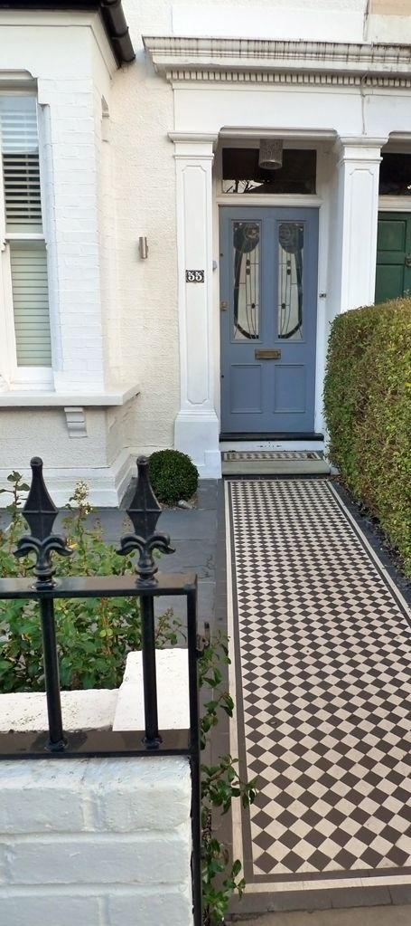black and white mosaic tile path with white painted wall with metal rail and iron gate balham london (3)