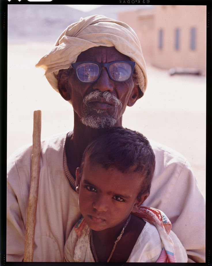 Let's go to the land of Black Pharaohs, Sudan.  Here a man with a young child. I love their incredible beautiful faces. Something timeless and universal at the same time. The only evidence of modernity is the eyewear that the old man is wearing, catching me in the reflection on glasses, proving that at this single moment, just once in our live, we were face to face in the land of Meroe.