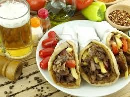 GYROS: pork meat roasted vertically and cut into thin slices, served with grilled pitta and tzatziki or wrapped as a souvlaki.