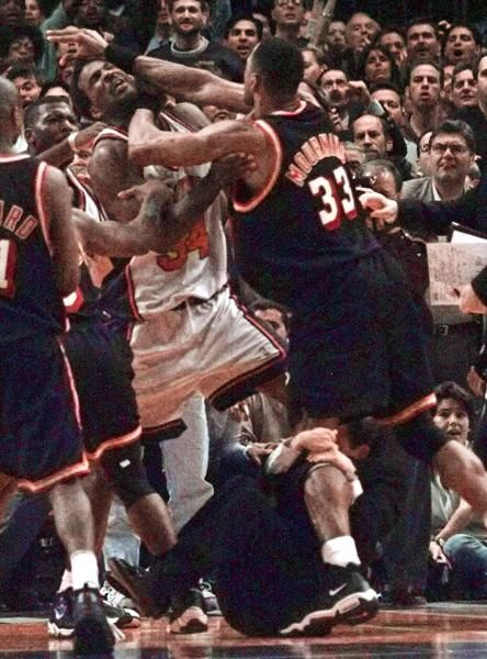 Miami Heat's Alonzo Mourning, right, and New York Knicks' Charles Oakley grapple as Knicks coach Jeff Van Gundy