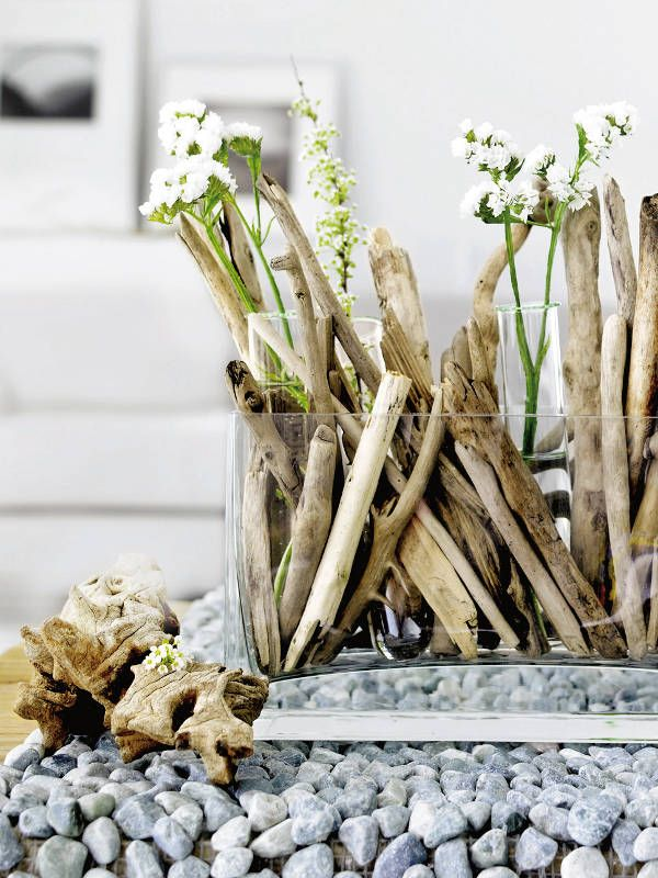 lovely driftwood in a glass vase paired with white flowers and pebbles - perfect for a beach themed tablescape or coastal style wedding decor