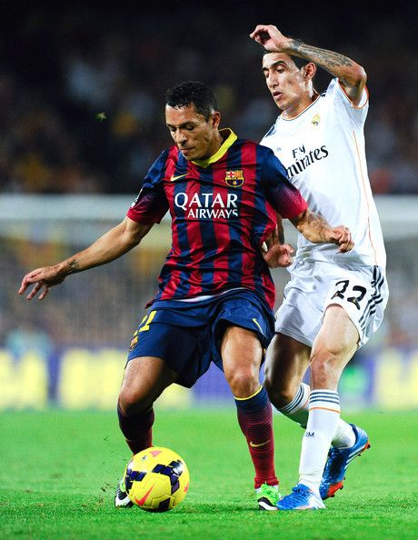 Adriano Correia of FC Barcelona (L) duels for the ball with Angel Di Maria of Real Madrid CF during the La Liga match between FC Barcelona and Real Madrid CF at Camp Nou on October 26, 2013 in Barcelona, Catalonia.