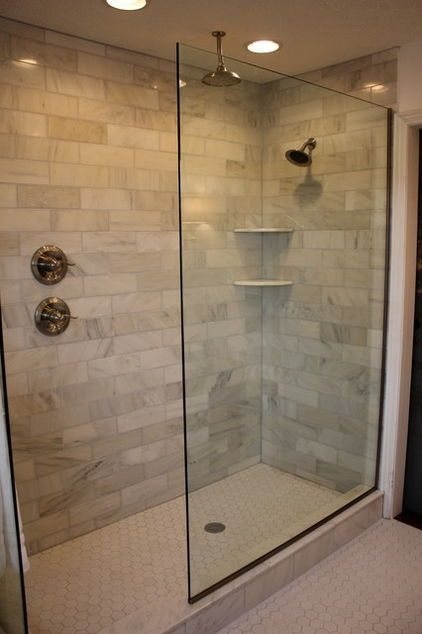 Clear glass shower divider and continuous flooring give the illusion of more room. Keep the look simple and uncluttered, since the room is not all that large.