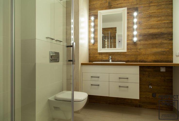 Aranżacja łazienki z prysznicem. Szklane drzwi prysznica dają efekt większej przestrzeni.