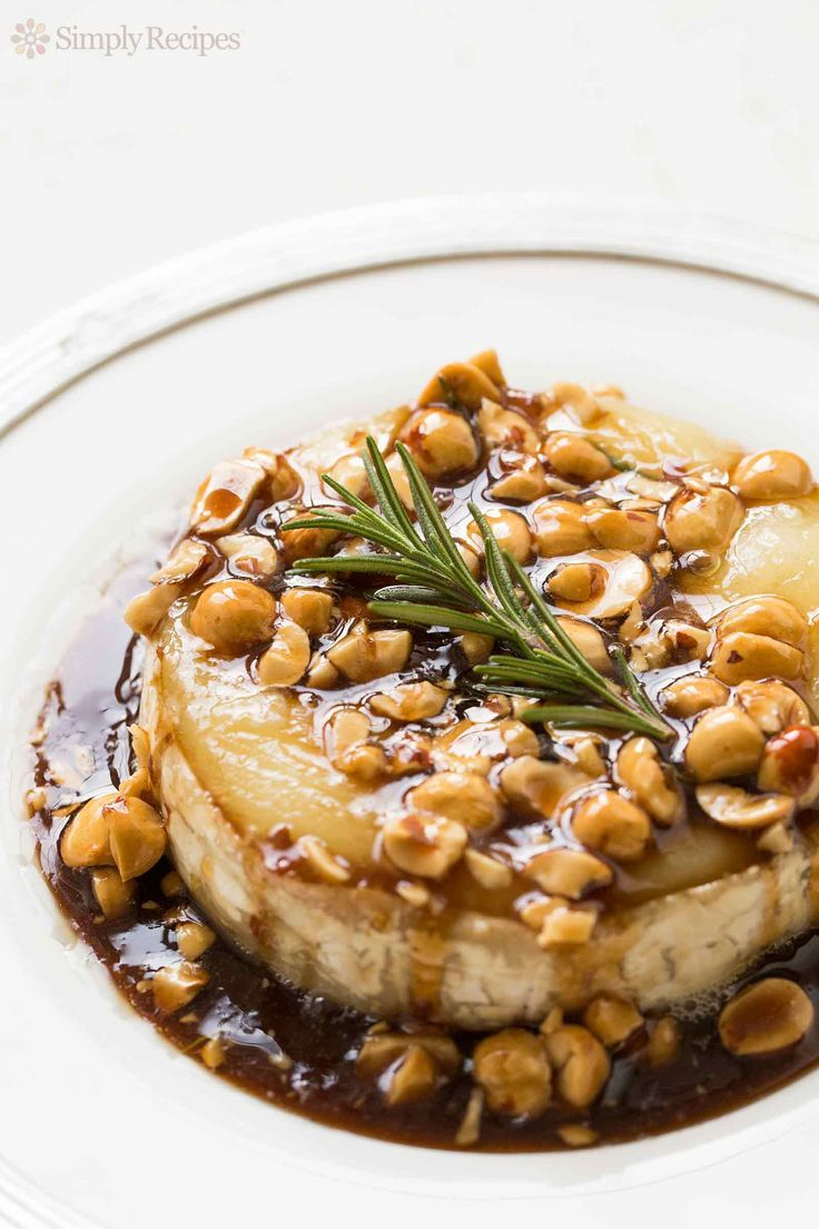 Festive Baked Brie! Drizzled with a sweet and sour honey sauce and toasted hazelnuts. Absolutely delicious with apple slices. On http://SimplyRecipes.com