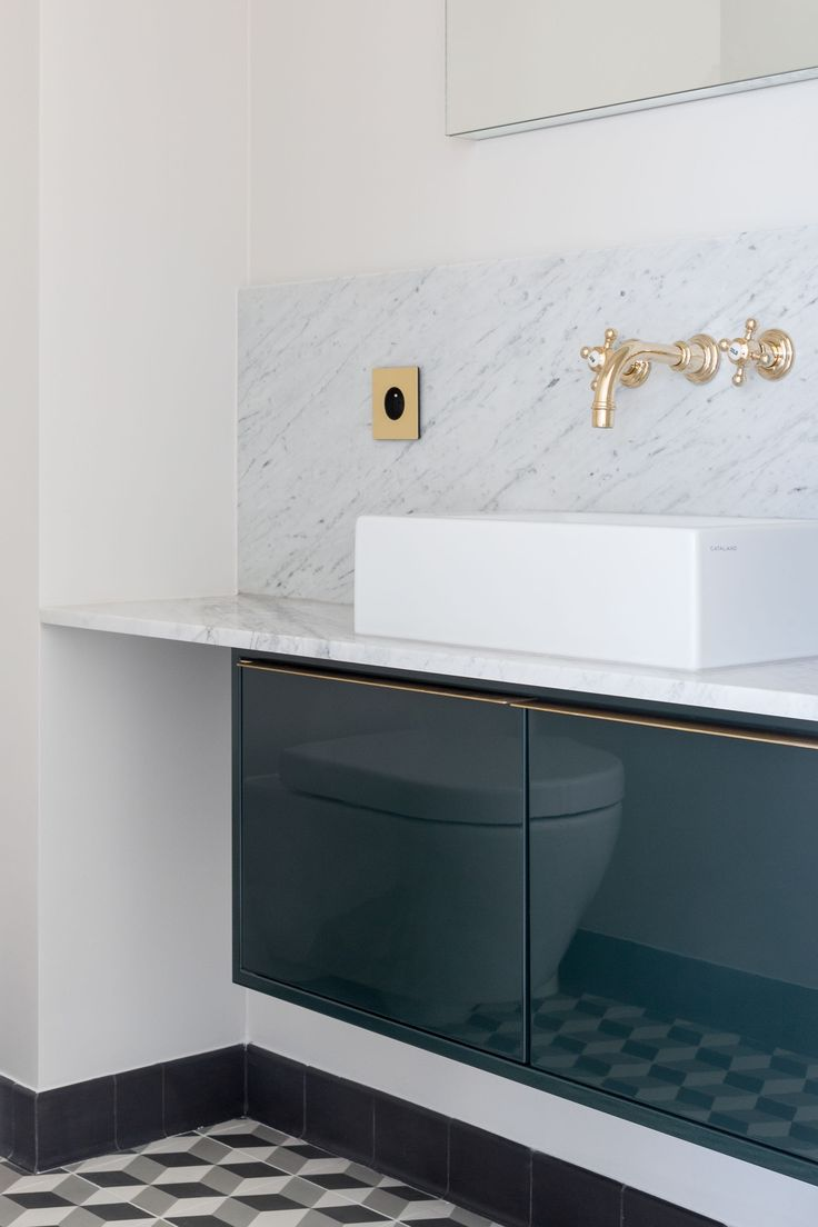 Marble washbasin with brass Dornbracht taps and high gloss cabinetry designed by Studio Mills.
