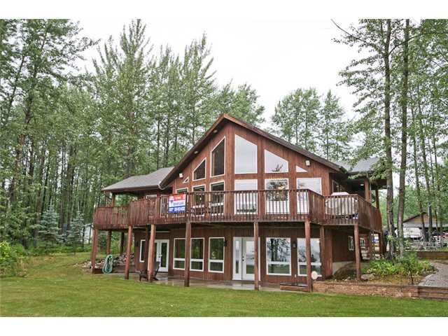 Custom built, lake front home in Buck Lake with Guest House & 4 Garage Bays.
