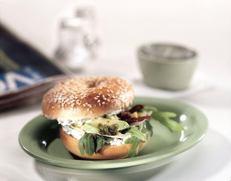 Bagel laktózmentes sajtkrémmel, paradicsommal, bazsalikommal és avokádóval Könnyen és gyorsan készíthetünk ízletes szendvicset, ha van kéznél bagel, laktózmentes sajtkrém és zöldségek.  Bagel laktózmentes sajtkrémmel.