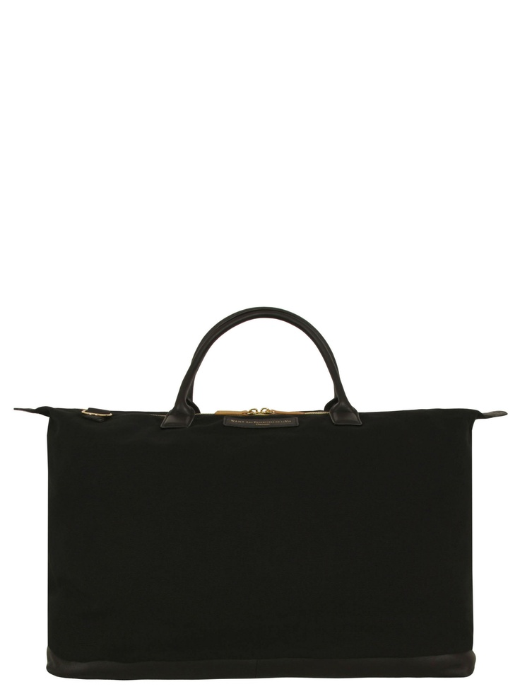 Want Les Essentiels de la Vie £260 at Coggles.com – Hartsfield, mens black organic cotton canvas tote bag with a leather base and rolled top handles. The bag also features a top zip fastening with contrast tan leather zip pulls, a detachable shoulder strap and golden embossed Want Les Essentiels de la Vie logo. The main compartment is partially lined with four black and white checked pockets.