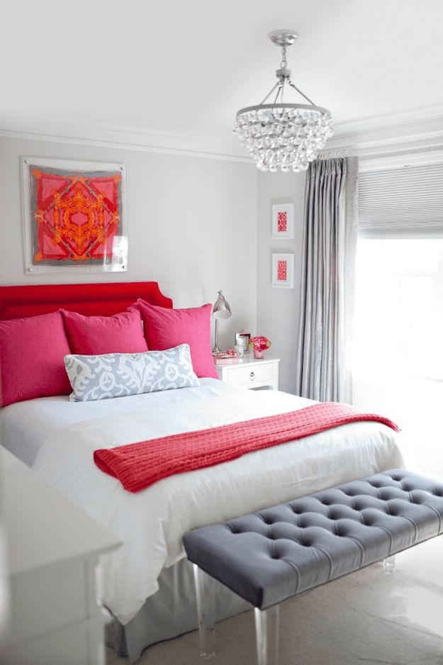 pale gray bedroom, bright red accents, hot pink accents, charcoal gray tufted bench, small crystal chandelier, bright red headboard, hot pink pillows, white bedding, pantone pink yarrow, pantone flame