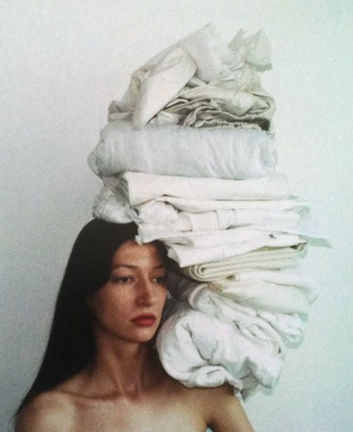 This photo is full of white. Woman looks so sad behind housework.