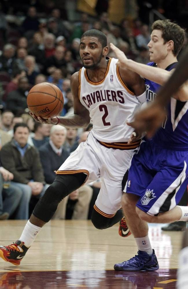 Cleveland Cavaliers' Kyrie Irving (2) drives past Sacramento Kings' Jimmer Fredette during the first quarter of an NBA basketball game Tuesd...