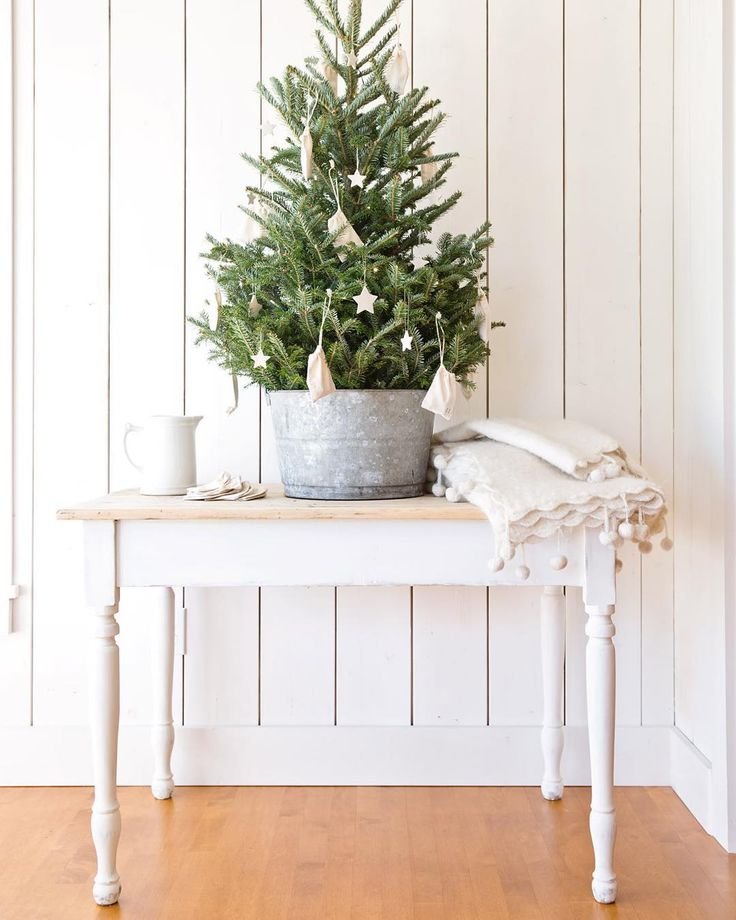 Charming farmhouse Christmas decor moment in a room with white shiplap, tree in galvanized pail and farm table - A Rosy Note.