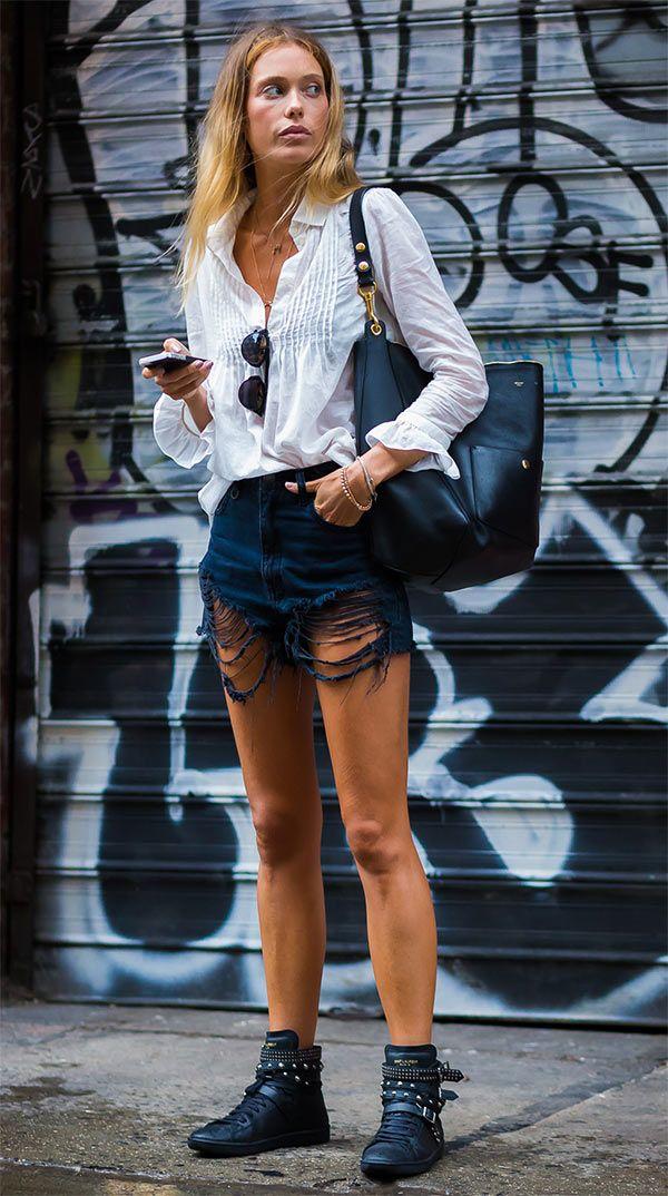Street style com camisa, short jeans a botinha preta com maxi bolsa.