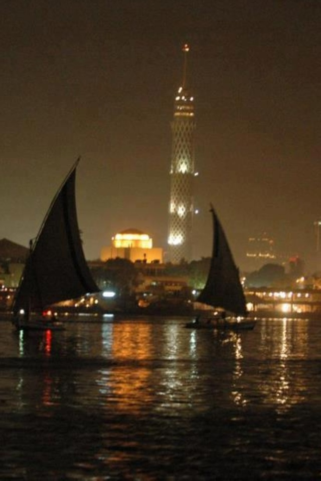The Cairo tower shines in the background as the boats sail past.