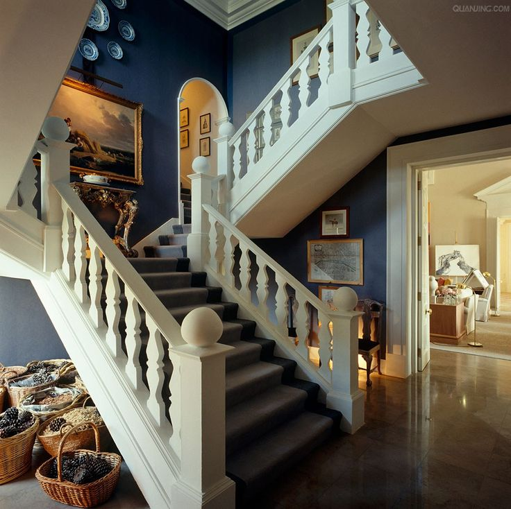 white carved staircase in bold blue entry in David Hicks home in England