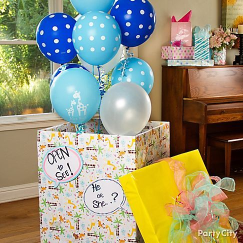 Easy, fun idea for the big reveal part of a gender reveal baby shower: Decorate a giant box, and fill it with blue or pink helium balloons. Lift the lid to share the news!