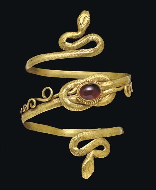 """A GREEK GOLD AND GARNET SNAKE ARMBAND   HELLENISTIC PERIOD, CIRCA LATE 4TH-3RD CENTURY B.C.   Formed from a stout strap, flat on the interior, carinated on the exterior, coiled into a spiral, the ends terminating in two coiling naturalistically-modelled snakes, the scales well detailed, the heads finely contoured, the bodies forming a """"Herakles knot"""" at the center, the tails looping and undulating outward along the lengths, the knot centered by an oval cabochon garnet in a plain bezel"""