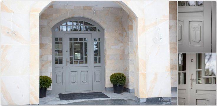 Ujęcie frontalne. Zbliżenie drzwi dębowych, zewnętrznych z bocznymi skrzydełkami oraz naświetlem. Drzwi ozdobione płaskorzeźbami, dwukolorowe. Od zewnętrznej strony szarość, a od wewnętrznej biel, która harmonizuje z resztą wnętrza. Oak exterior doors, grey on the outside, white inside, relief and glass