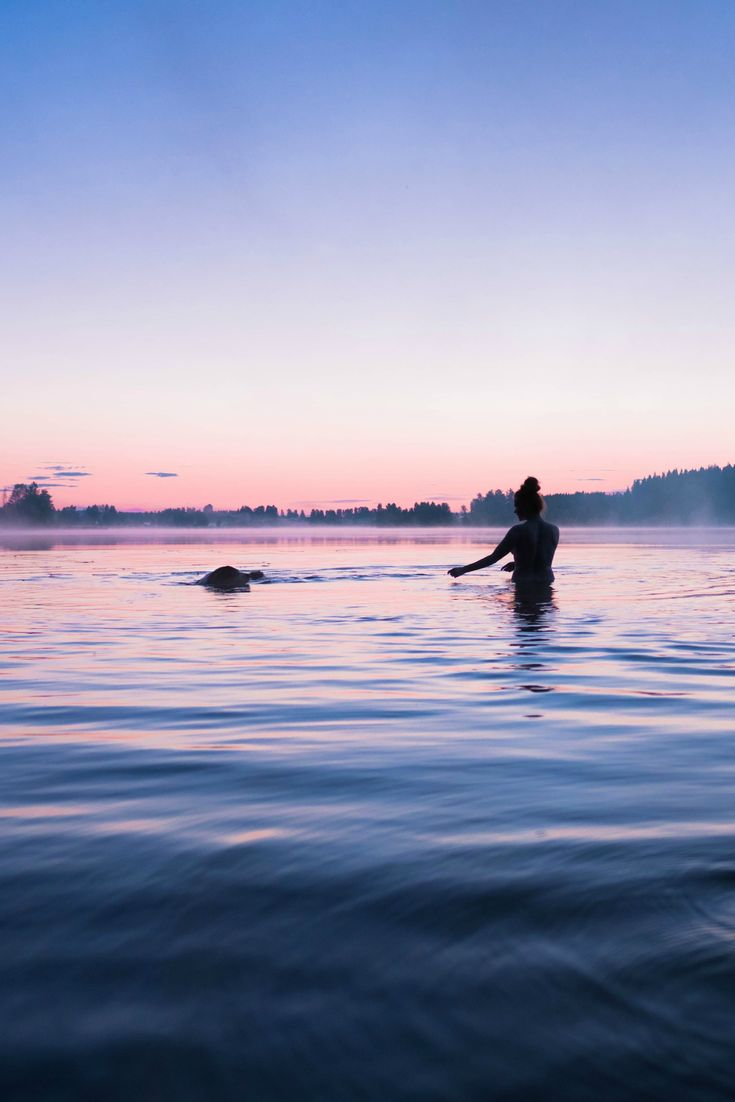 Summer sunset photography. Doggie and his mom swimming. Outdoor adventures with dog.