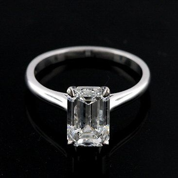 "This elegant 14k white gold solitaire engagement ring is pictured with one 2Ct emerald cut diamond set in delicate ""claw"" prongs. The shank is rounded and high polish."