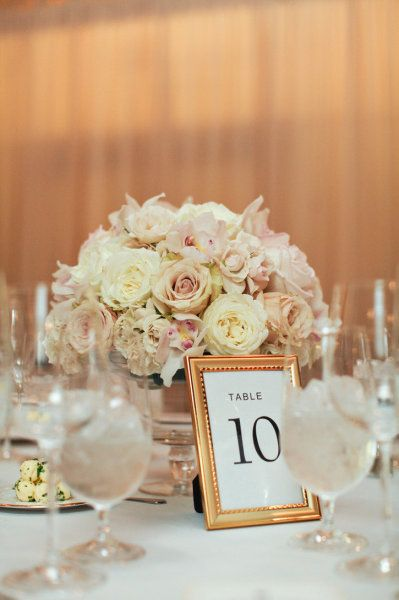 Clear glass container with gold table number frames
