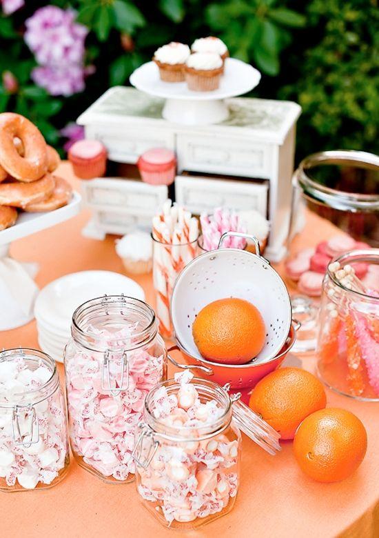 Een sweet table waar ook roze met oranje is gecombineerd. Net als snoep en fruit.