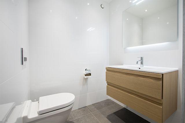 Väggar i vitt kakel med glansig yta och golv i grå klinker. En vägg i det stora badrummet täcks av natursten och förstärker spakänslan. Duschen är snarare ett duschrum, med en vägg i glas och en väldig takdusch. Också den stora bastun har en vägg helt i glas. I en avskild del av badrummet finns en vägghängd toalett och ett vägghängt handfat med en underdel i ljust trä.