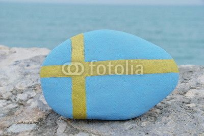 Flag of the Kingdom of Sweden on a stone with sea background