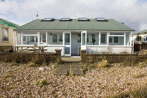 Made up of two extended 1950s railway carriages, this beach-front detached bungalow with sea views across the Channel is on a private residential estate in the Pagham Harbour nature reserve at Bognor Regis, West Sussex.