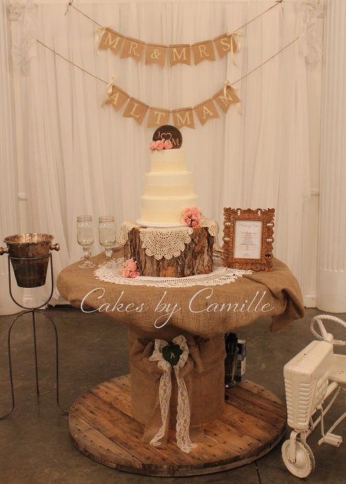 Vintage wedding cake display, burlap, lace, and rustic log all work together to give an antique feel.