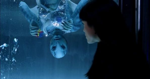 Abe Sapien is floating in an aquarium upside down holding a Rubik's Cube only solved for two sides. A girl named Liz Sherman is sitting in front of the aquarium.