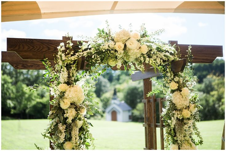 Wedding ceremony arch with white flowers and greenery