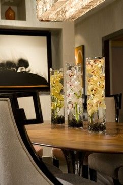 A Long, Tubular Vase Filled With Stones And Water Is Perfect For An Orchid  Stem. The Centerpiece Is Created By Simply Repeating The Look With A Trio  Of ...