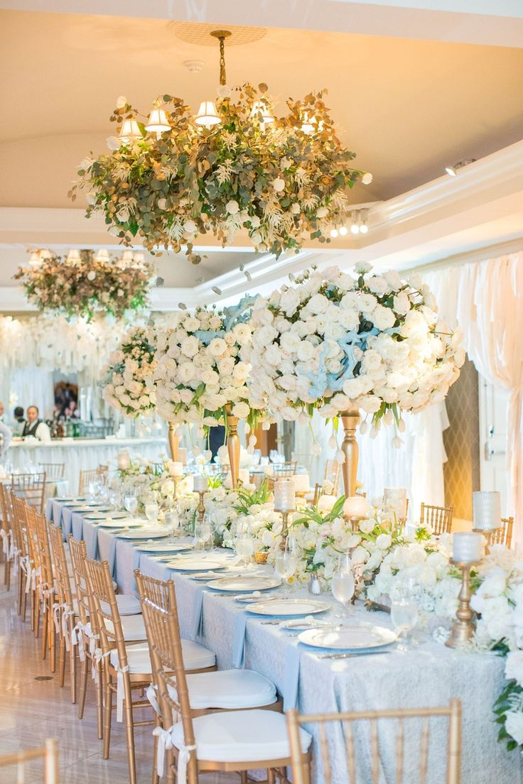 Tall Centerpieces on Long Table + Green Chandeliers | Photo: Thisbe Grace Photography.