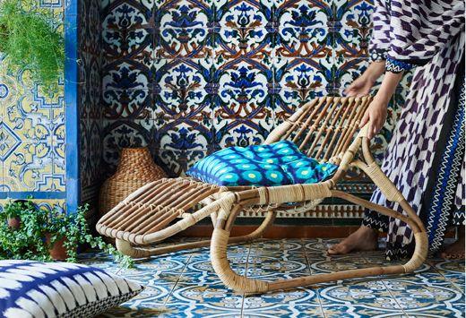 Liten hvilestol i rotting med runde former. Her med ei fargerik pute med batikkinspirert mønster.